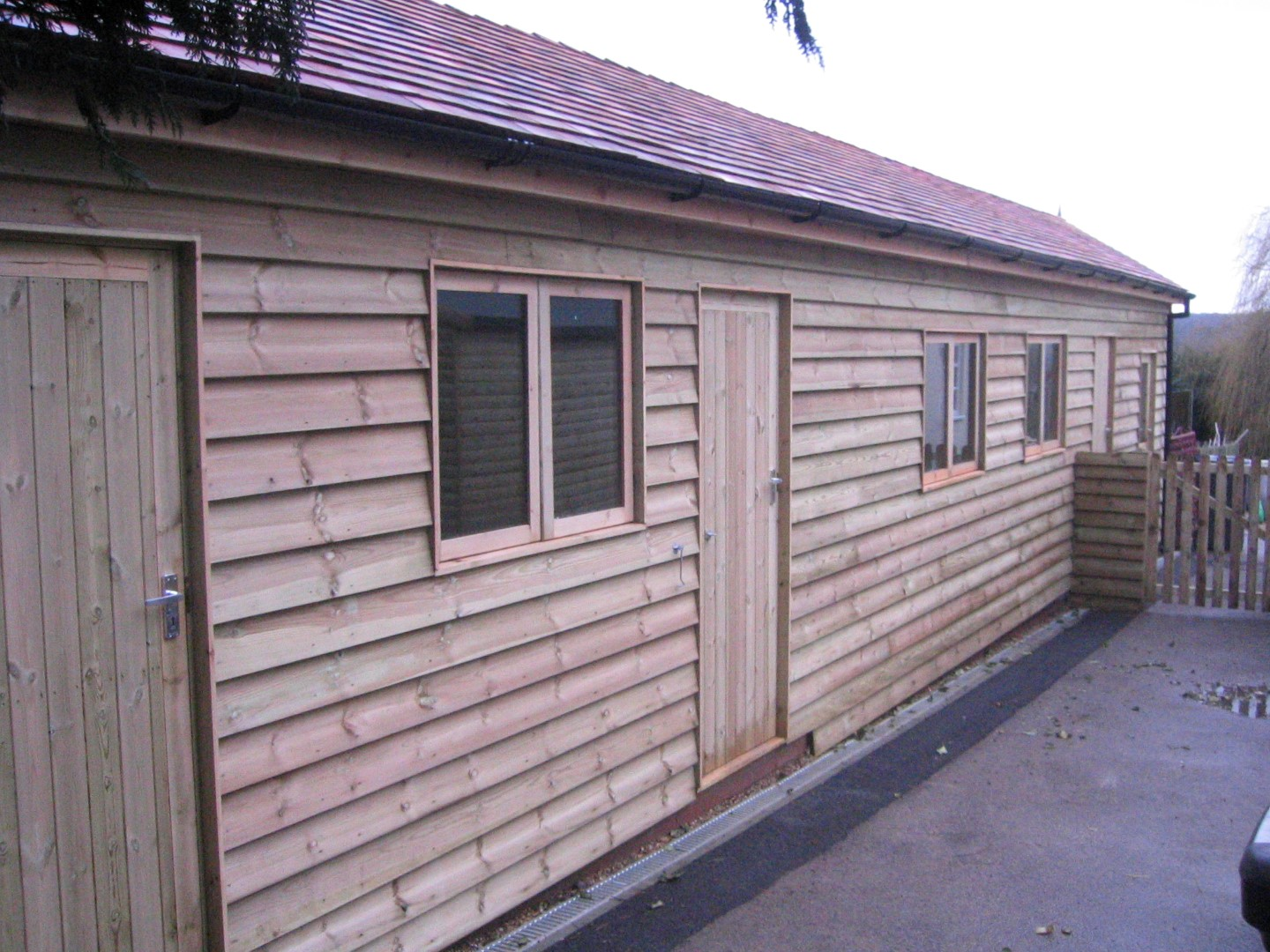 Heavy duty feather edge external cladding, Quinneys joinery double glazed windows, cedar wood shingles to the roof